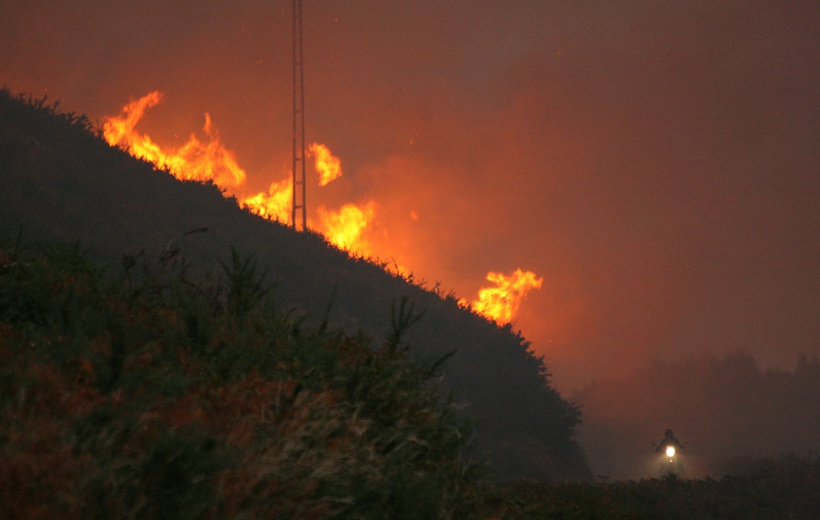 What conditions cause large wildfires in Portugal and Spain?